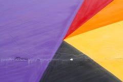 Mur peint violet, rouge, jaune et noir coloré avec des fissures Photographie stock