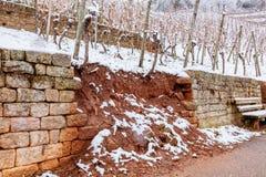 Mur pierre à macadam dans l'eau de vignoble et des dommages de neige image libre de droits