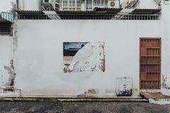 Mur propre blanc avec le mur rouge rouillé avec la trace déchirée d'affiche de la rue de George Town Penang, Malaisie image libre de droits