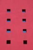 Mur rouge avec de petites fenêtres Photo stock