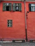 mur rouge avec les fenêtres vertes Sibiu |Roumanie Photographie stock libre de droits