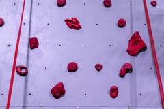 Mur rouge et gris d'escalade avec le crochet de carabiner et s'élever photo stock