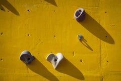 Mur s'élevant artificiel jaune avec des prises Image stock