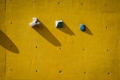 Mur s'élevant artificiel jaune avec des prises Photos libres de droits