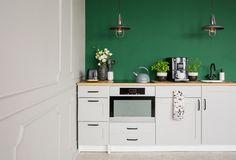 Mur vert vide avec l'espace de copie dans la cuisine élégante avec les meubles, les usines et la machine blancs de café images stock