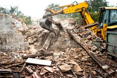 mura di cemento industriali di demolizione di caricamento del bulldozer e dell'escavatore Fotografia Stock Libera da Diritti