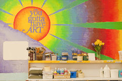 Mural in art classroom. A large, colorful wall mural and art supply shelf in a school art classroom royalty free stock images