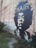 Mural on a Brick Wall Hair. This great graffiti Mural showing off the Hendrix hair on a great distressed brick wall Stock Photos