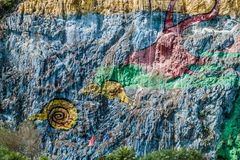 Mural de la Prehistoria The Mural of Prehistory painted on a cliff face in the Vinales valley, Cuba stock photo