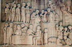Mural de talla tailandés complejo - gente tailandesa de la ayuda de la actividad del rey Imagen de archivo libre de regalías