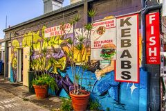 Mural graffiti wall art of the side of a kebab shop and fish and chips royalty free stock images