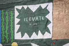 Elevate -- be love - mural. Mural in green and white on a building in downtown Des Moines, Iowa, reading Elevate be Love stock images
