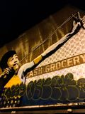 Mural painting of kid using slingshot. Unique street art of young boy aiming a slingshot with the words cash grocery and graffitti underneath stock photos