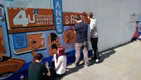 Mural painting. Teenagers painting a city centre mural Stock Photography