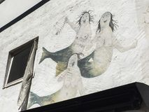 Three mermaids on a white wall. Mural painting of three mermaids on the wall of a fisherman´s house Royalty Free Stock Photography