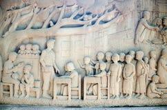 Murale di scultura tailandese complesso - gente tailandese di aiuto di attività di re Fotografia Stock