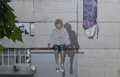 Murales graffiti. Beautiful murals on a Soviet-style concrete building, representing a girl sitting on a beam, Chisinau Moldova stock photo