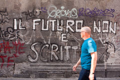 Murales neaples italy. A passerby reads an inscription on a wall of spaccanapoli, neaples italy Royalty Free Stock Images