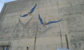 Murals. On side of building in Heraklion. Crete. Greece. Two flying figures with large blue wings Royalty Free Stock Photography