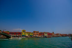 MURANO,意大利- 2015年6月16日:一点色的房子全景Murano的河边界的,通过的小船  库存图片