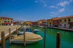 MURANO,意大利- 2015年6月16日:在Murano市的木口岸,在运河的停放的小船和在边的色的房子 免版税库存照片
