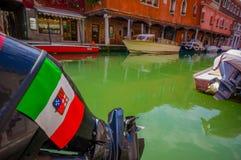 MURANO,意大利- 2015年6月16日:意大利旗子和盾在一个小船引擎在绿色水上在Murano运河 免版税库存图片