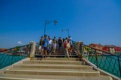 MURANO, ΙΤΑΛΊΑ - 16 ΙΟΥΝΊΟΥ 2015: Άνθρωποι που διασχίζουν μια συμπαθητική παλαιά γέφυρα στην πόλη Murano, στο δευτερεύοντα νερό κ Στοκ εικόνες με δικαίωμα ελεύθερης χρήσης