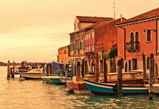 Murano boats in Venice. Boats in front of buildings on Murano island in Venetian Lagoon during the sunset, Venice, Italy stock photo
