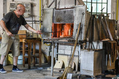 Murano Glass maker. Murano glass is glass made on the Venetian island of Murano, which has specialized in fancy glasswares for centuries. A traditional master Stock Photo