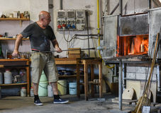 Murano Glass maker. Murano glass is glass made on the Venetian island of Murano, which has specialized in fancy glasswares for centuries. A traditional master Royalty Free Stock Images