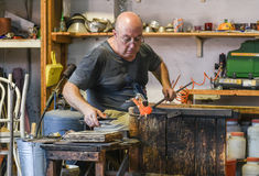 Murano Glass maker. Murano glass is glass made on the Venetian island of Murano, which has specialized in fancy glasswares for centuries. A traditional master Royalty Free Stock Photos