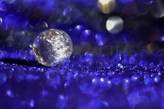 Murano glass silver bead on a blue shiny background with bokeh stock photography