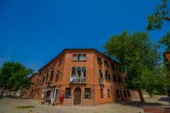 MURANO, ITALIA - 16 DE JUNIO DE 2015: Casa anaranjada en la esquina de la calle de Murano, de la gente en el balcón y de un peque Fotos de archivo libres de regalías