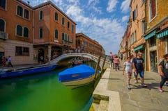 MURANO, ITALIE - 16 JUIN 2015 : Murano lapident le pont au milieu des canaux, du bateau bleu de transport et des turists Photos stock
