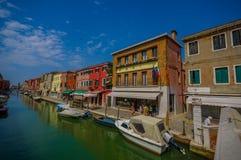 MURANO ITALIEN - JUNI 16, 2015: Den Murano gatan med traditionella hus och shoppar framme av trevliga vattenkanaler Fotografering för Bildbyråer