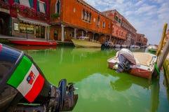 MURANO ITALIEN - JUNI 16, 2015: Italien flagga och sköld på en fartygmotor ovanför ett grönt vatten i Murano kanaler Arkivbild
