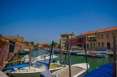 MURANO ITALIEN - JUNI 16, 2015: Olika fartyg som förutom parkerar på hus för folk för Murano kanaler, trevlig sikt i solig dag Arkivbild