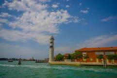 MURANO, ITALIEN - 16. JUNI 2015: Weißer Leuchtturm auf Murano, weite Ansicht vom Wasser, threes auf den Seiten mit der Stadt Lizenzfreie Stockfotografie