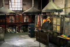 Interior of an artistic glassworks in Murano, Venice. Ancient furnace for blown glass processing. Murano, Italy - April 24, 2017: Interior of an artistic stock image