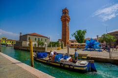 MURANO, ITALY - JUNE 16, 2015: Brick tower with the clock and glass sculpture on the side, fishingman using boat Royalty Free Stock Photos
