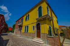 MURANO, ITALY - JUNE 16, 2015: Yellow pinturesque house at the beggining of a beautiful alley with colored houses Royalty Free Stock Image