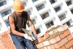 Murare som installerar tegelstenar med murslevhjälpmedlet Arkivbild