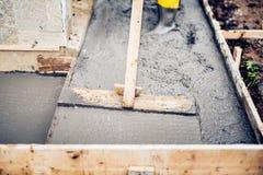 Murarearbetare som bygger och jämnar ett första lager av det nya konkreta golvet på hustrappa och trottoarer, konstruktionsplats royaltyfria foton