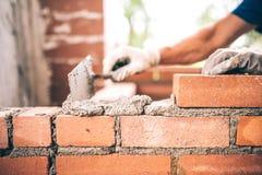 Murarearbetare som installerar tegelstenmurverket på den yttre väggen med murslevspackeln royaltyfri fotografi
