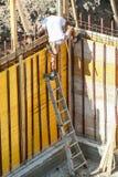 Muraremurare eller snickarearbetare med skalan Job Security Arkivbilder