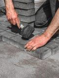 Muraren bygger trottoar Manh?nder l?gger lager av tegelstenar royaltyfri bild