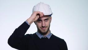 Muratore bello che indossa un casco bianco sulla sua testa Priorità bassa bianca archivi video