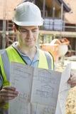 Muratore On Building Site che esamina le piante della casa Immagine Stock Libera da Diritti