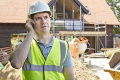 Muratore On Building Site che per mezzo del telefono cellulare Fotografie Stock