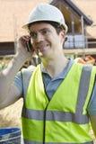 Muratore On Building Site che per mezzo del telefono cellulare Fotografia Stock